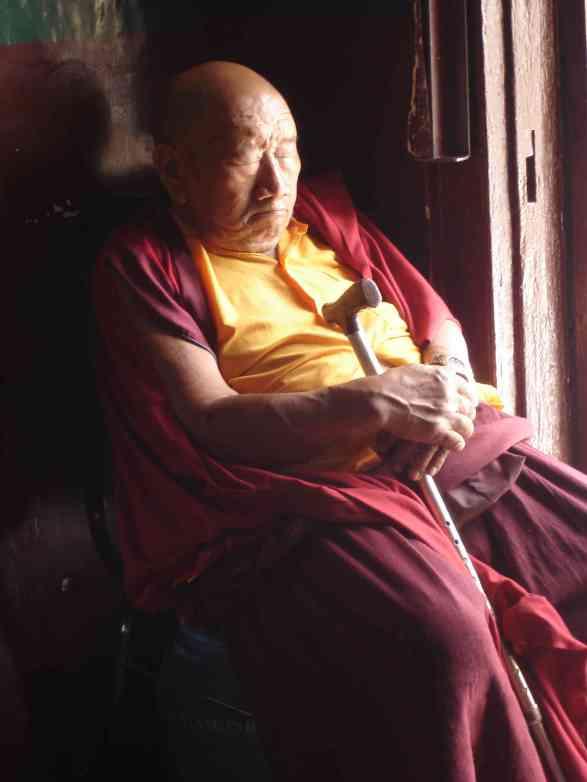 An elderly Tibetan monk takes a nap