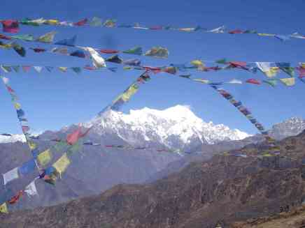 An enormous mass of mountain framed by prayer flags around Langtang