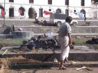A worker stokes the fire of a funeral pyre