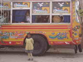 A girl standing in front of a typical Pakistani bus