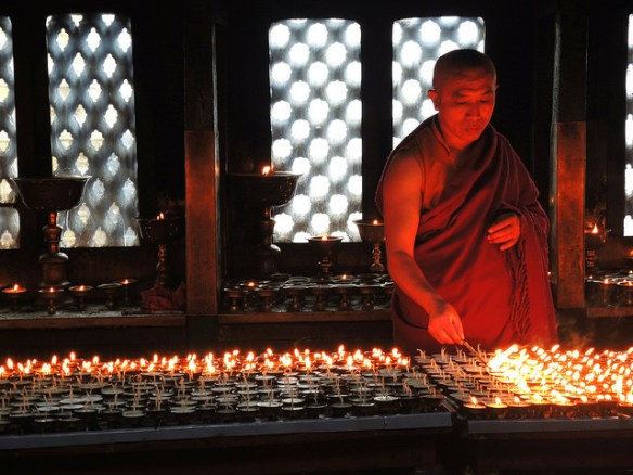 A Monk of Kathmandu lighting candles. Photograph by Güldem Üstün via Flickr