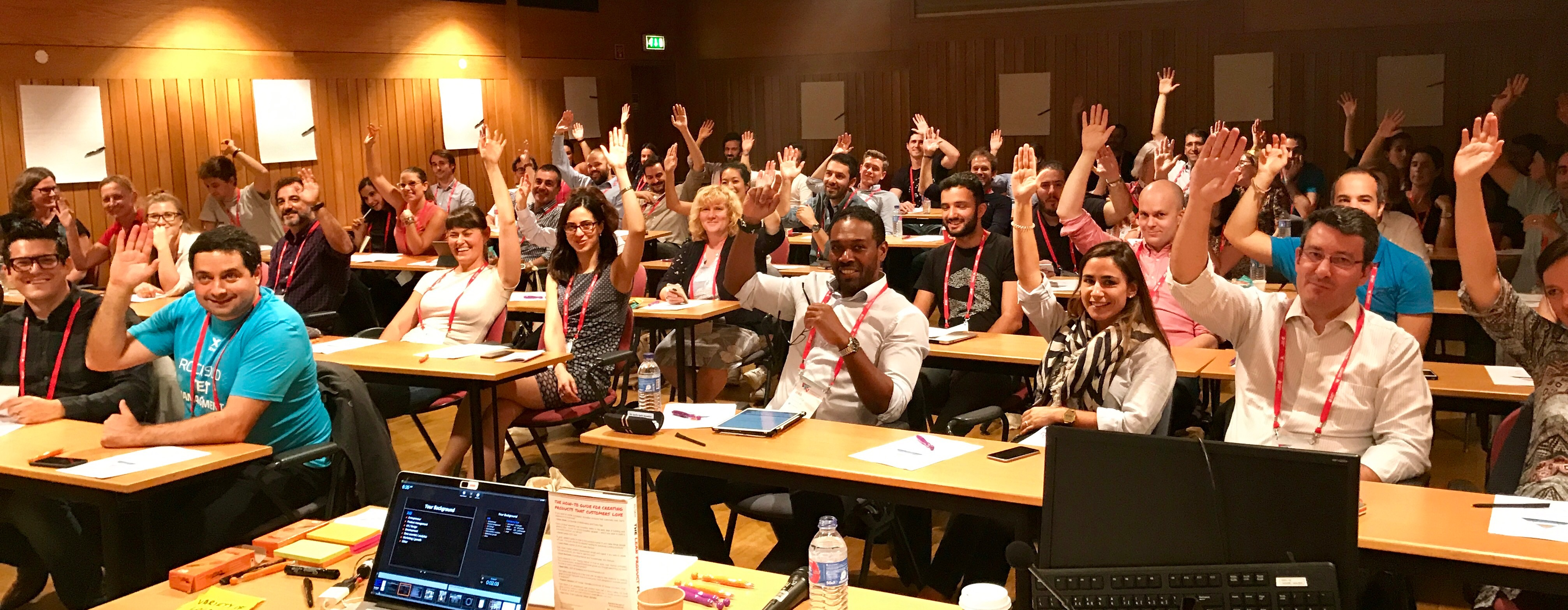 A group of workshop attendees raising their hands to participate and engage with Dan.
