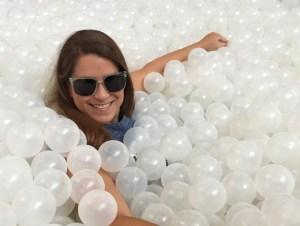 Dana Allen-Greil at a Building Museum exhibit full of white plastic balls