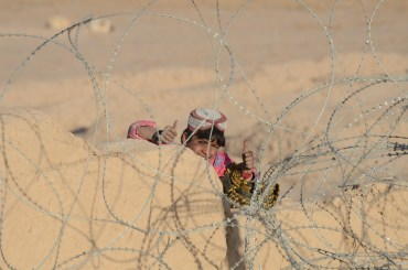 An Afghan boy climbs the wall surrounding FOB Bullard to get his picture taken