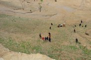 The kids scrambling up the hill to get close to the wall - they want candy & pens