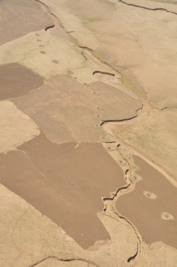 fields in the high desert with the holes of the karez visible