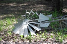 A windmill Dad built a long time ago lays bent on the ground. It has since been repaired and once again stands in the yard as it had for nearly 40 years