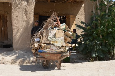an overloaded wheelbarrow parked at the only shop in the bazaar