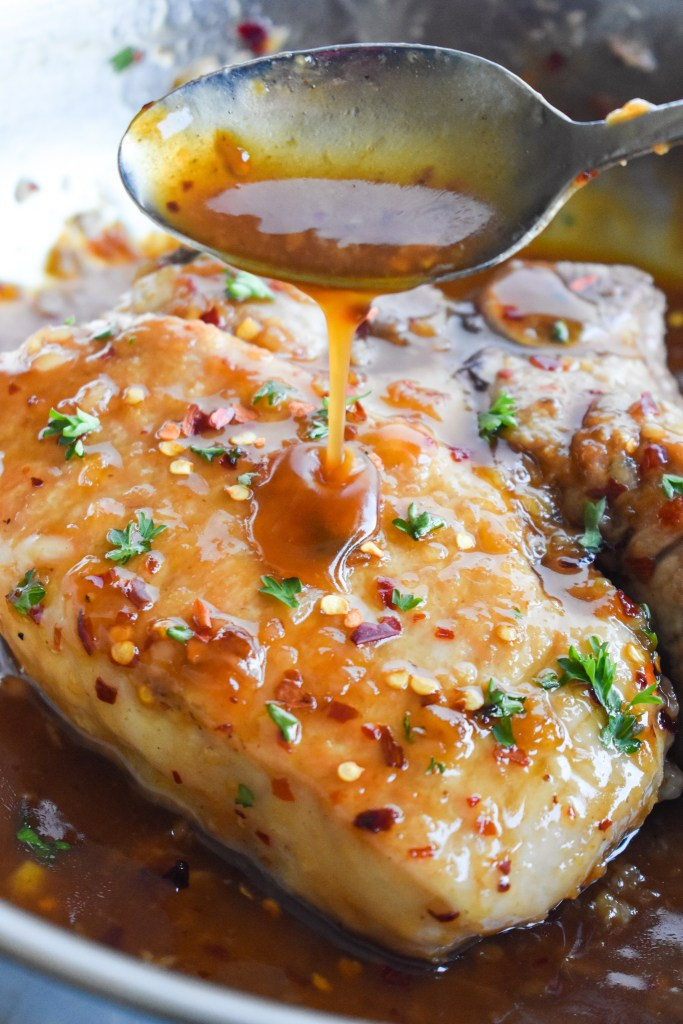 Sauce being poured over a honey garlic pork chop