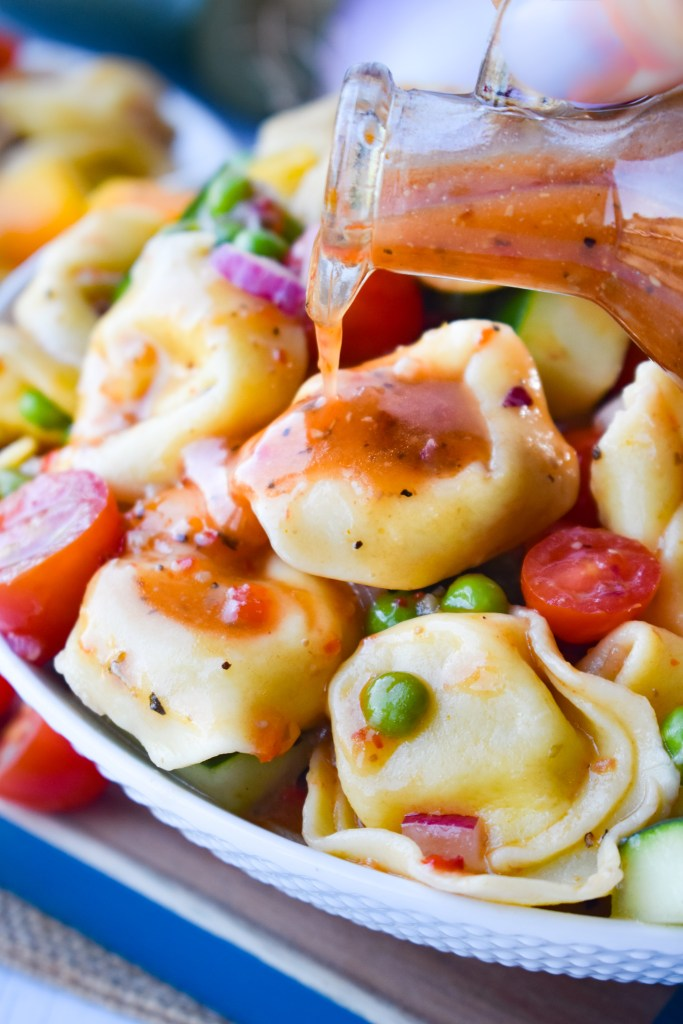 tortellini pasta salad with dressing being poured over it