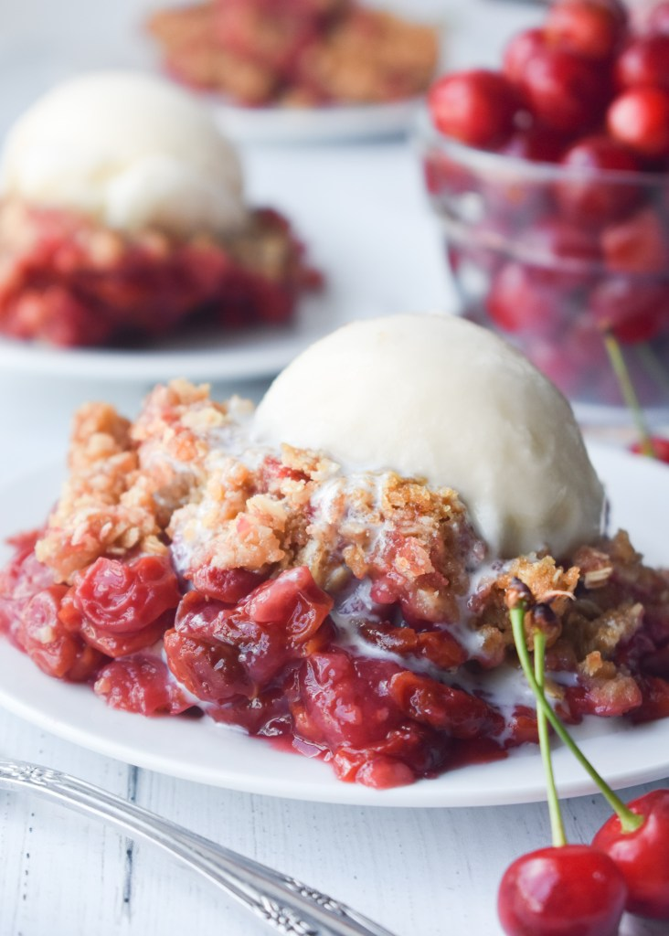 Scoop of cherry crisp on a white plate with vanilla ice cream