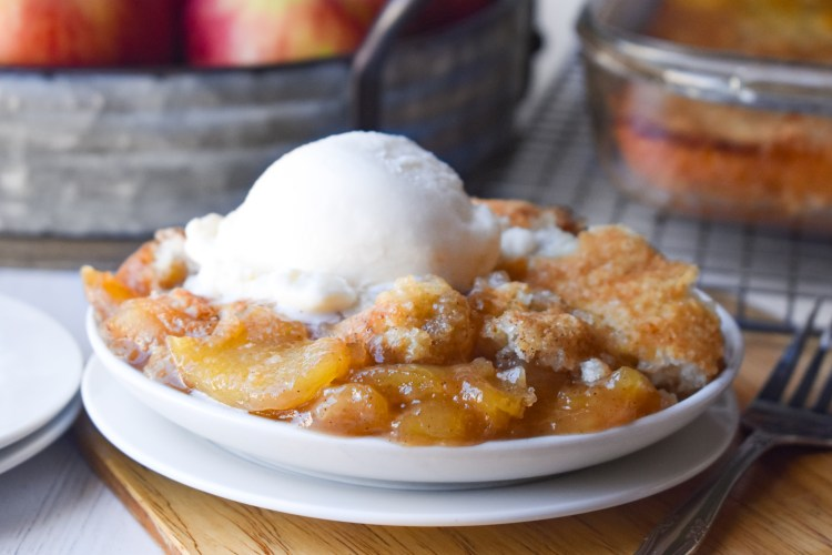 Caramel Apple Cobbler on a white plate with vanilla ice cream