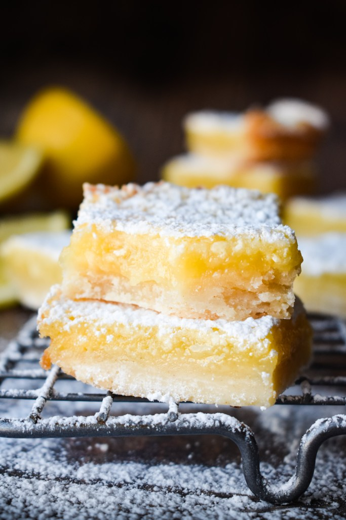 Lemon bars stacked up on a wire rack