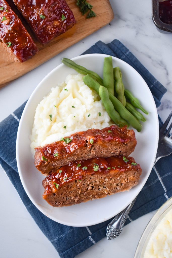 Plate with two slices of meatloaf, mashed potatoes and green beans.