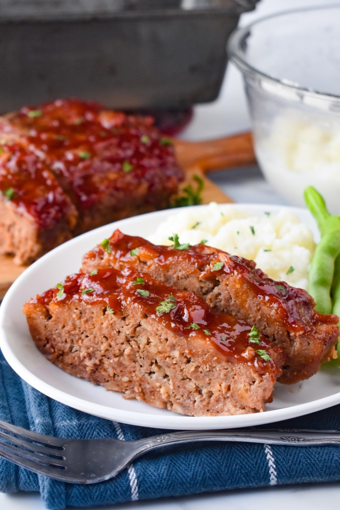 Meatloaf on a plate with mashed potatoes and green beans