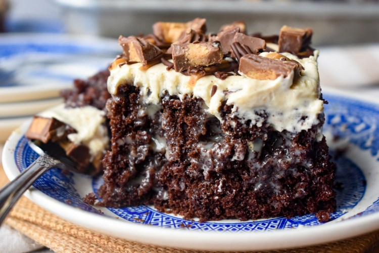 Piece of Chocolate Peanut Butter Poke Cake with a forkful out of it