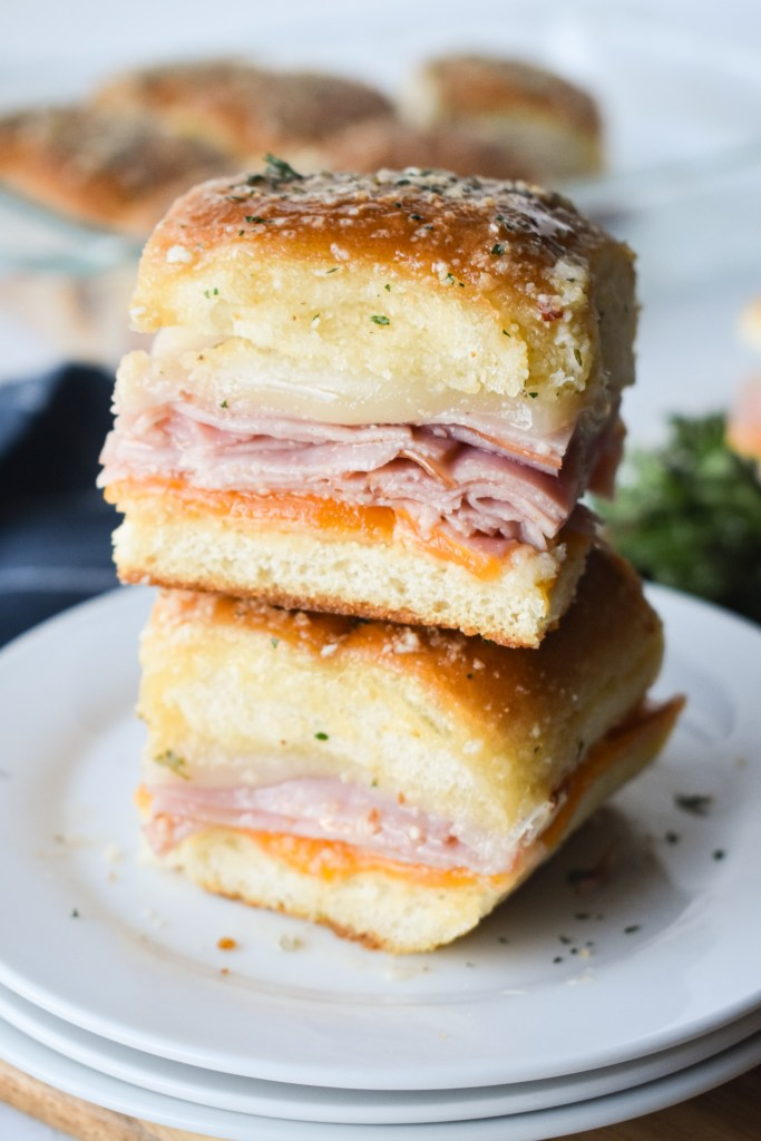 Two Ham & Cheese Sliders stacked on a white plate