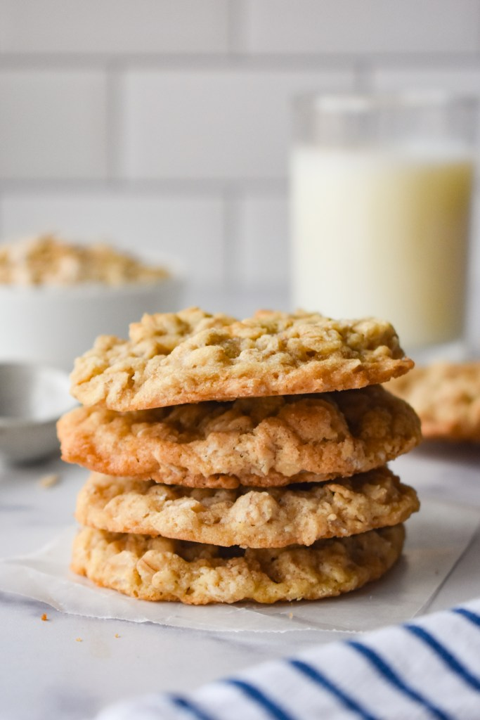 Stack of four chewy oatmeal cookies with milk