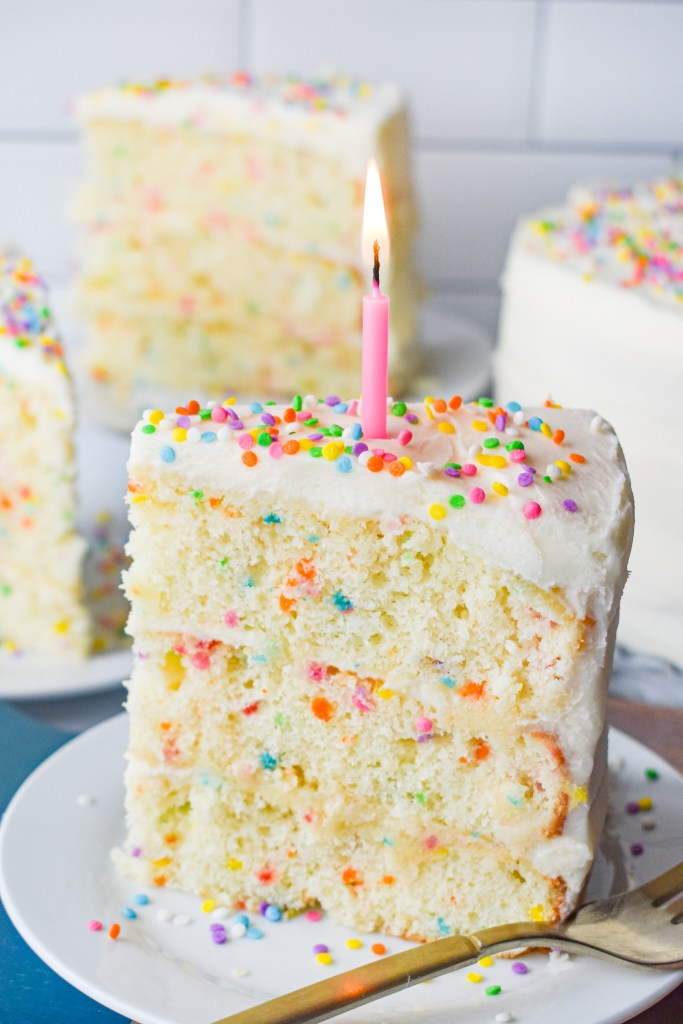 Layered funfetti cake with a candle lit on top