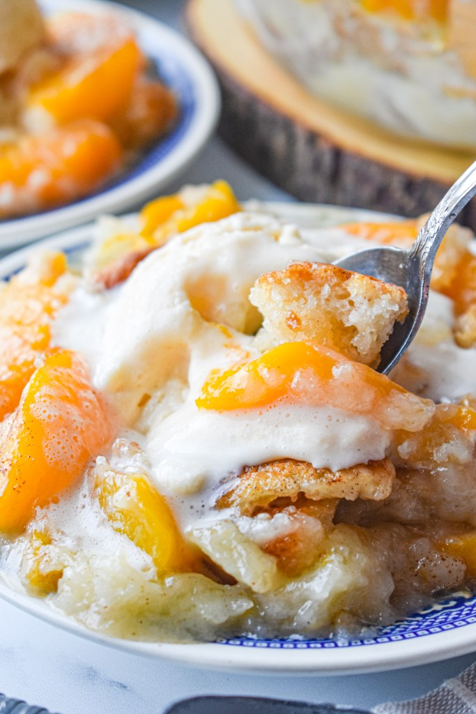 Peach Cobbler on a plate with vanilla ice cream with a spoon in it