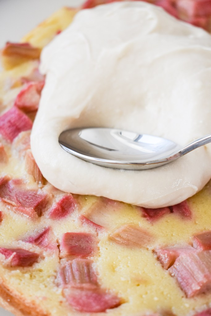 Cream Cheese frosting being spread over the rhubarb custard bars