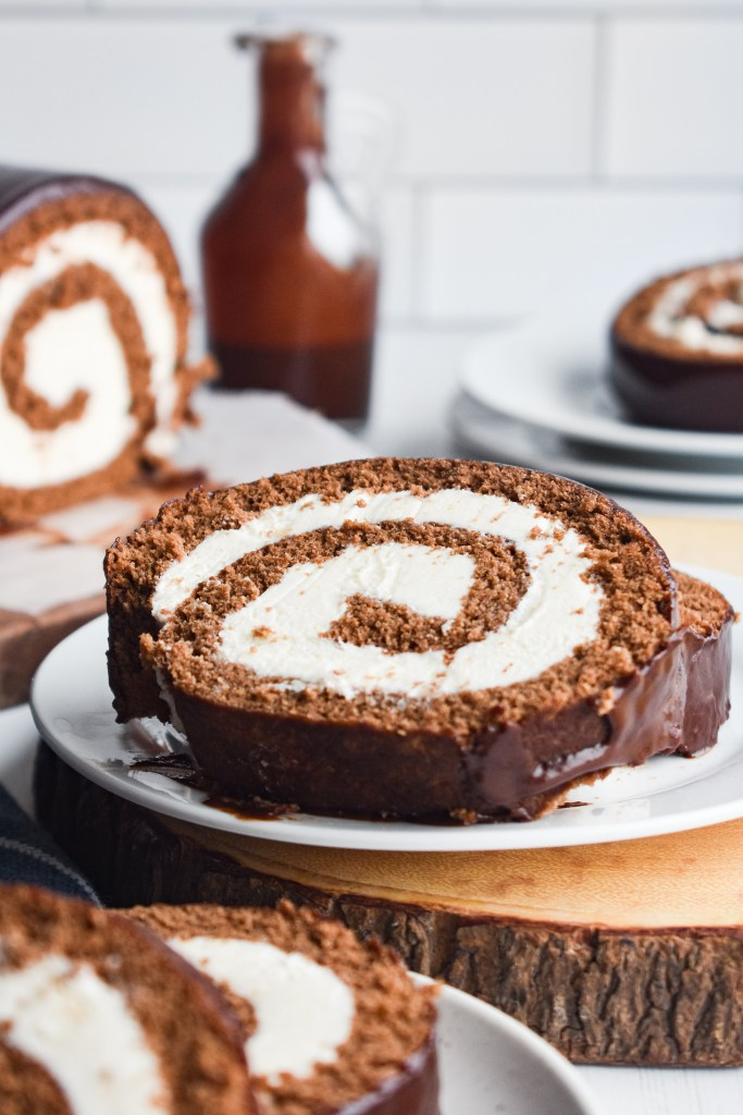 Two slices of swiss roll cake on a white plate