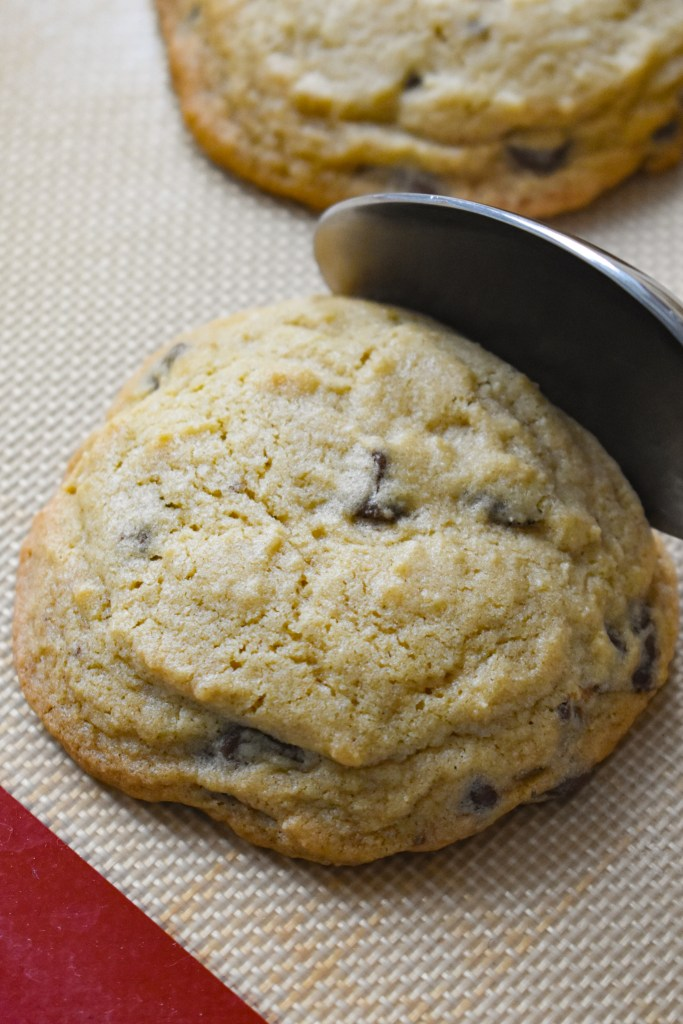 Using a spoon to press the edges of a cookie in toward the center