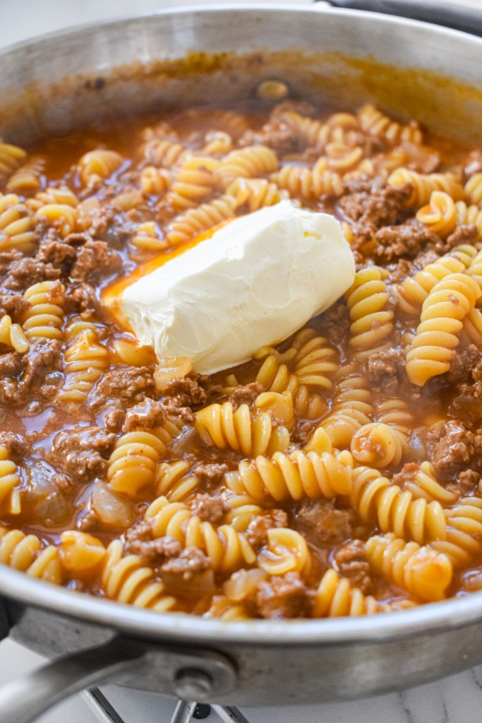 Adding the cream cheese into the pasta.