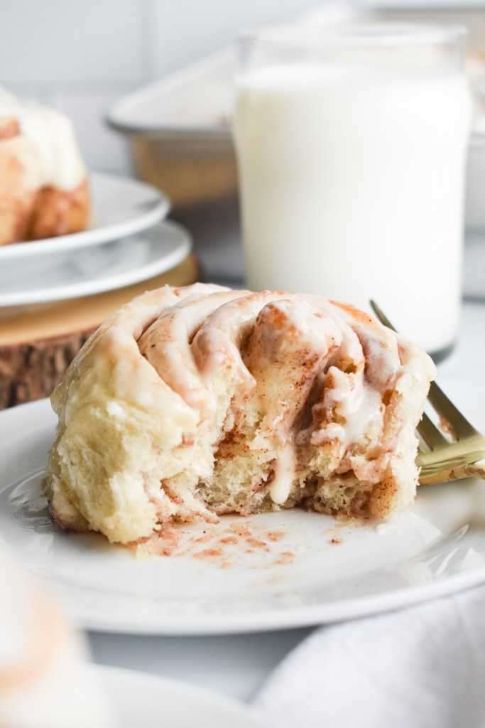 Cinnamon roll with a bite out of it on a white plate with a glass of milk in the background.