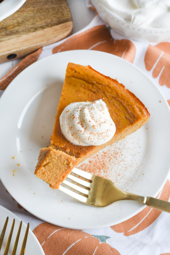 crustless pumpkin pie on a white plate with a fork & whipped topping