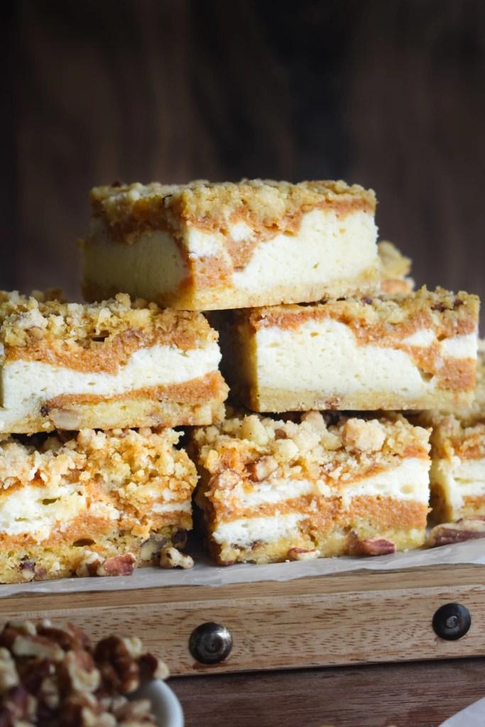 pumpkin cheesecake bars on a wooden platter