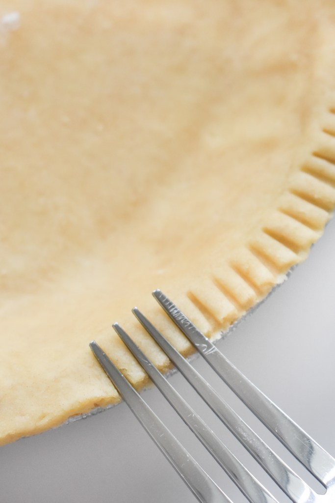 decorating the edge of a pie crust with a fork