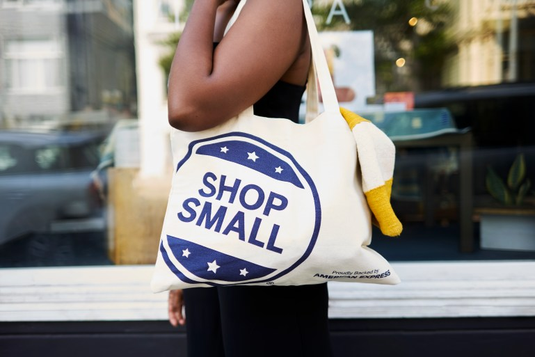 Woman with Shop Small tote bag walking past local storefronts.