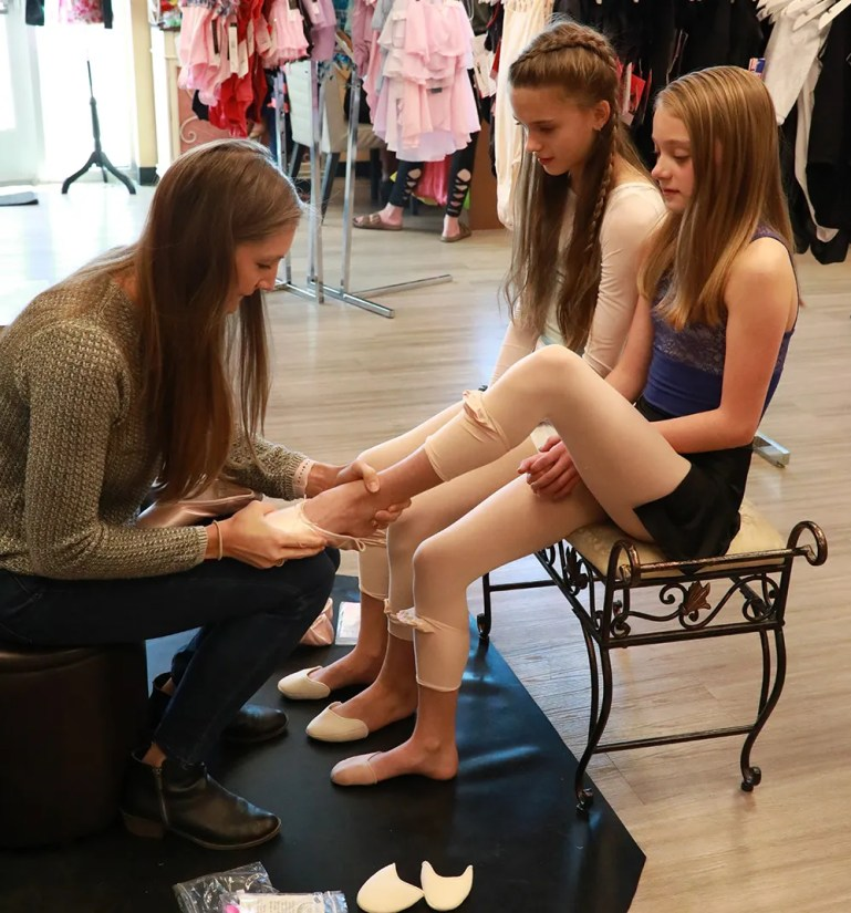 Two seated girls having pointe shoes fitted at the Colorado Springs store Balerina Boutique.