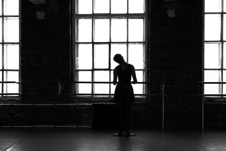 Dancer at barre looking out large paned window.
