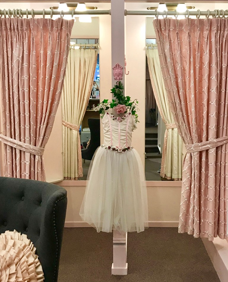 A romantic tutu costume hangs on a decorative hanger between two dressing rooms, with mirrors and pink curtains