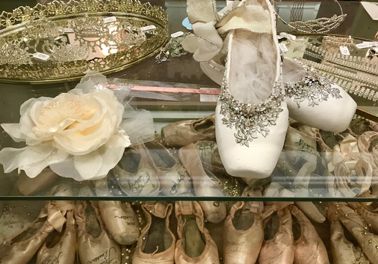 Decorated pointe shoes on top of counter. Below, many vintage signed pointe shoes from NYCB principals.