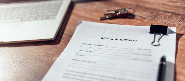 Blank rental agreement sitting on a desk with pen and set of keys.