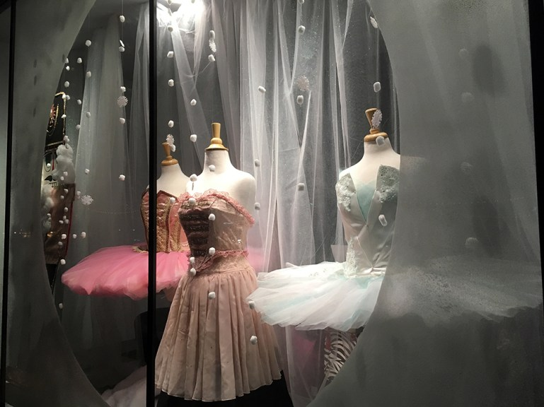 Three mannequins in The Dance Bag store window wearing tutus, framed by a snow-globe like circle.