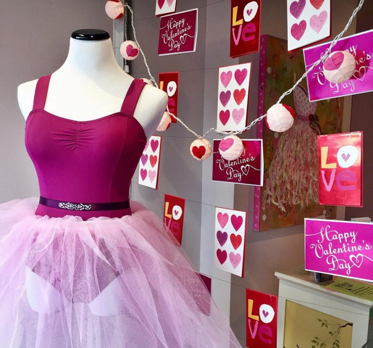 Mannequin with burgundy red leotard and pink tulle skirt at Saratoga Dance, Etc. Valentine's Day cards form a backdrop.