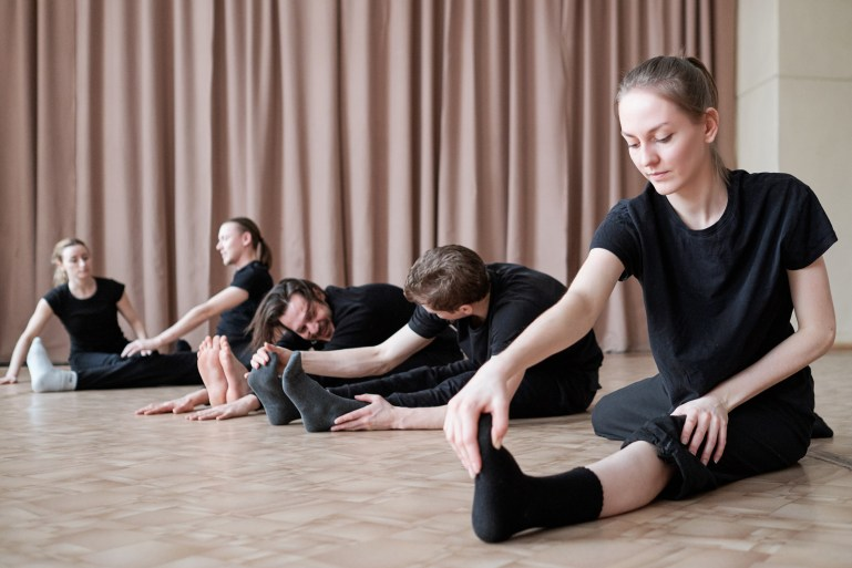 Dancers, wearing black leggings and leotards, stretching together on the floor.
