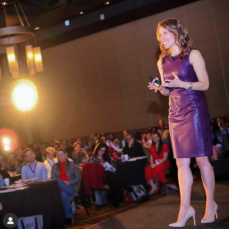 Dance studio owner and motivational speaker Misty Lown delivers a seminar presentation on stage before a live audience.