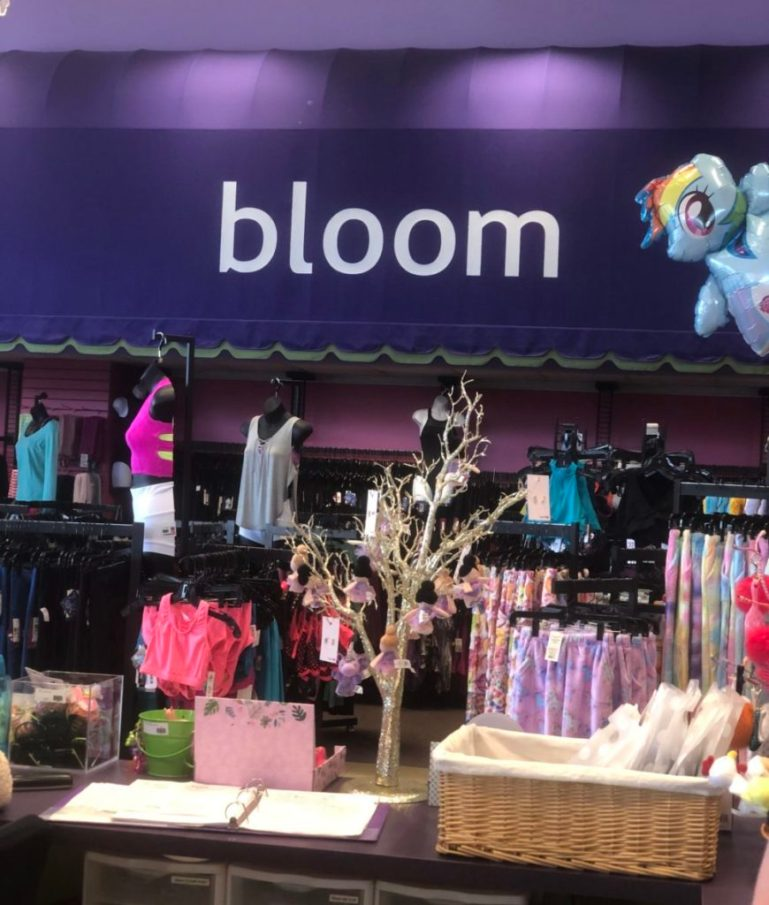 Purple canopy on wall of Bloom Dancewear store, with racks of dancewear below, half mannequins on top of them and accessories on the cash desk in the foreground.