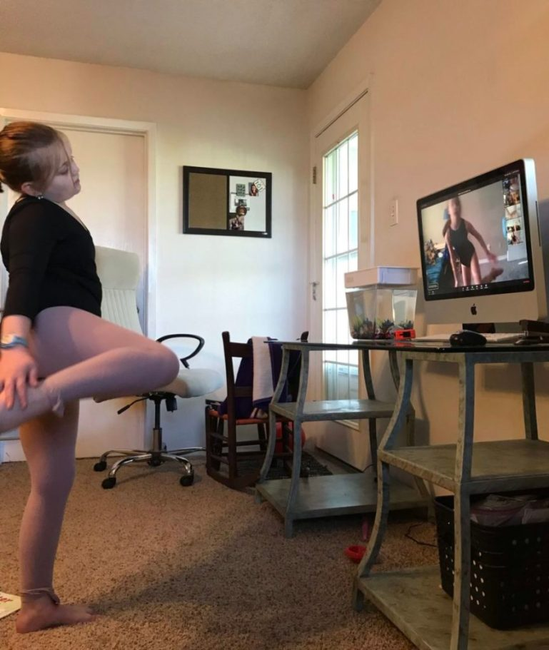 Young dancer in front of computer screen taking dance class.
