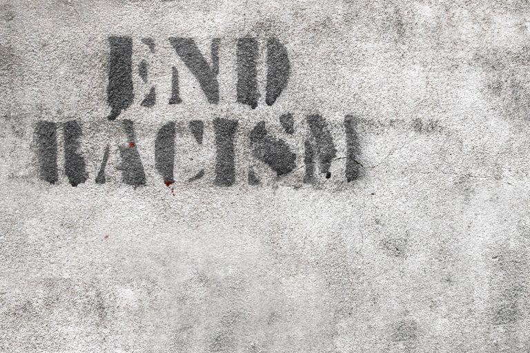 "Graffiti on a concrete wall says ""end racism."""