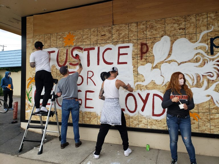 "4 people in masks paint the mural on the side of Ananya Dance Theatre that says ""Justice for George Floyd."""