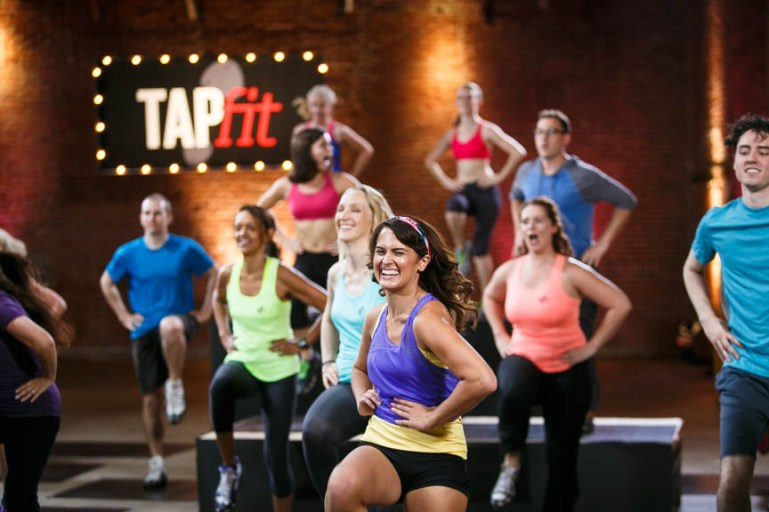 "A group of smiling dancers in colorful outfits raise one knee in the air. A sign behind them says ""tapfit"""