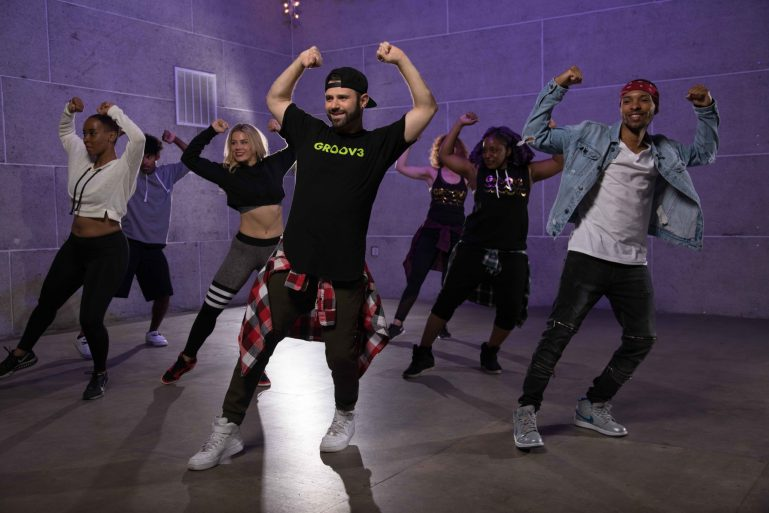 "A man in a ""groov3"" shirt leads a class of 6 dancers. they wear trendy hip hop outfits, and have their arms raised above their heads, making fists."