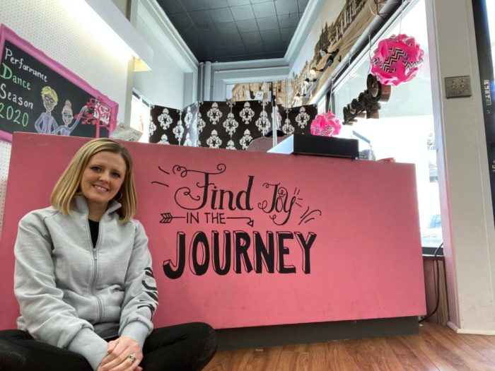 "Jennifer Velasquez sitting on floor cross-legged in front of the pink cash desk, which has the words ""find joy"