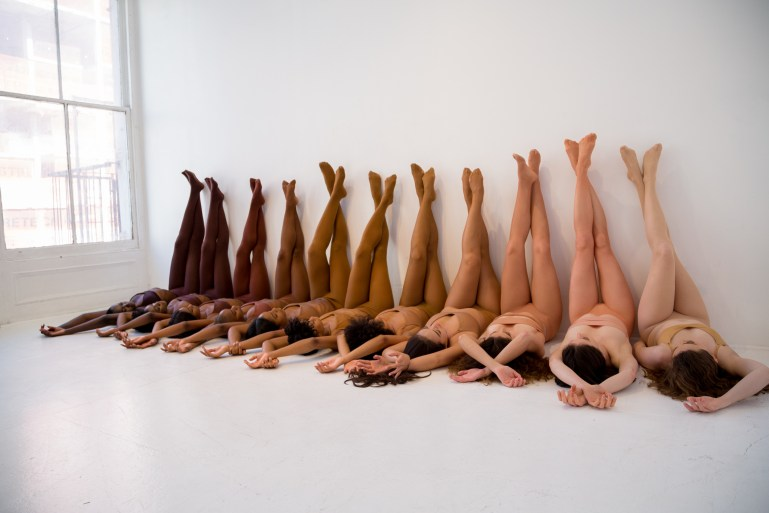 Group of models lying on floor with legs up on wall, displaying the range of nude shades available in Nude Barre tights and undergarments.